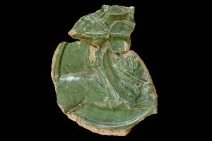 Fragment des Innenfelds einer Blattkachel mit Ritter beim Gestech in rundem Medaillon mit losem Tauband, grün glasiert, um 1450, Emmendingen, Hochburg