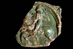 Fragment einer Blattkachel mit Ritter beim Gestech in einer Arkade mit akanthusblattbesetzten Zwickeln, grün glasiert, um 1450, H. 13,0 cm, Br. 12,5 cm, Lörrach, Museum am Burghof, urspr. Burg Rötteln
