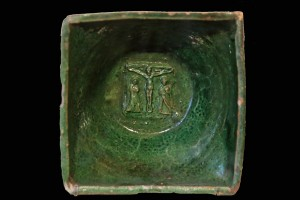 Fragment einer Napfkachel mit glatt abgestrichenem Rand und einer Kreuzigungsgruppe auf dem Boden, grün glasiert, 16. Jh., H. 18,0 cm, Br. 18,0 cm, Innsbruck, Tiroler Volkskundemuseum