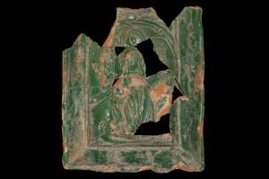 """Fragment einer Nischenkachel mit geschlossenem Vorsatzblatt mit der knienden, lesenden Maria aus einer zweiteiligen Verkündigungsdarstellung vom Typ 1, grün glasiert, H. 20,5 cm; Br. 18,0 cm; Oberrhein, um 1450, Karlsruhe-Durlach, Privatbesitz, urspr. vom Areal """"Lederkromer"""""""