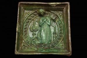 Fragment einer Blattkachel mit taubandbesetztem Medaillon und der betenden Maria aus einer zweiteiligen Verkündigungsdarstellung, grün glasiert, 2. Hälfte 15. Jh., Linz, Oberösterreichisches Landesmuseum