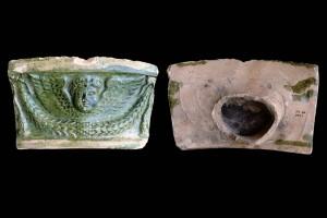 Fragment einer Gesimskachel mit geflügeltem Puttenkopf über lorbeerblattbesetztem Feston, grün glasiert, zweite Hälfte 17. Jh., Ettlingen, Albgaumuseum, urspr. Ettlingen, Klösterle