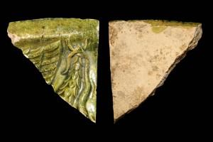 Fragment einer Gesimskachel mit geflügeltem Puttenkopf über lorbeerblattbesetztem Feston, grün glasiert, zweite Hälfte 17. Jh., H. 7,6 cm, Br. 7,4 cm, Speyer, Historisches Museum der Pfalz, urspr. Hardenburg