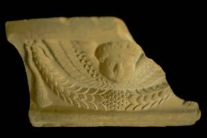 Fragment einer Gesimskachel mit geflügeltem Puttenkopf über lorbeerblattbesetztem Feston, unglasiert, zweite Hälfte 17. Jh., Heilbronn, Städtische Museen