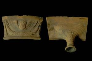 Fragment einer Gesimskachel mit geflügeltem Puttenkopf über lorbeerblattbesetztem Feston, graphitiert, zweite Hälfte 17. Jh., H. 8,5 cm, Br. 14,5 cm , Neudenau, Museum