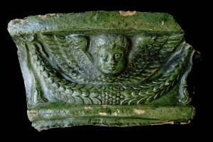 Fragment einer Gesimskachel mit geflügeltem Puttenkopf über lorbeerblattbesetztem Feston, grün glasiert, zweite Hälfte 17. Jh., H. 11,5 cm, Br. 20,0 cm, Baden-Baden Steinach, Museum