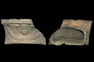 Fragment einer Gesimskachel mit geflügeltem Puttenkopf über lorbeerblattbesetztem Feston, graphitiert, zweite Hälfte 17. Jh., H. 9,5 cm, Br. 17,2 cm, Speyer, Historisches Museum der Pfalz
