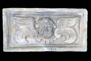 Fragment einer Blattkachel mit geflügeltem Puttenkopf, graphitiert, 17. Jh., H. 16,0 cm ; Br. 31,5 cm, Wiesbaden, Sammlung Nassauischer Altertümer