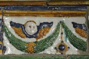 Fragment einer Gesimskachel mit geflügelten Puttenköpfen über lorbeerblattbesetzten Festons, mehrfarbig glasiert, 17. Jh., Innsbruck, Tiroler Volkskundemuseum