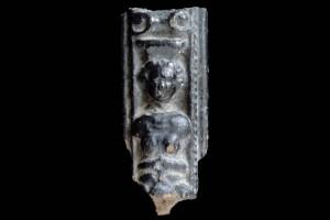 Fragment einer Leistenkachel mit Karyatidenpfeiler über quasthaltender Maske, dunkelbarun galsiert, 17. Jh., H. 11,0 cm, Br. 5,5 cm, Rastatt, Archäologisches Landesmuseum Baden-Württemberg, Zentrales Fundarchiv, urspr. Alpirsbach, Kloster