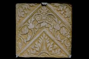 Fragment einer Bodenfliese mit Tapetendekor mit Akanthusrosetten und rechtwinkligem, rankenbesetztem Band, gelb glasiert, Anfang 17. Jh., H. 18,0 cm, Br. 18,0 cm, Saverne, Musée de Saverne