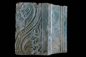 Fragment einer über Eck geführten Blattkachel mit Tapetendekor mit Maske zwischen einem schuppenbesetzten Kielbogen, grün glasiert, 17. Jh., H. 16,0 cm, Br. 18,0 cm, Staufen, Museum