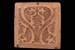Fragment des Models einer Blattkachel mit Tapetendekor mit Maske zwischen einem schuppenbesetzten Kielbogen, unglasiert, rückseitig datiert 1711, H. 25.5 cm, Br. 25,5 cm, Landshut, Staatliche Fachschule für Keramik